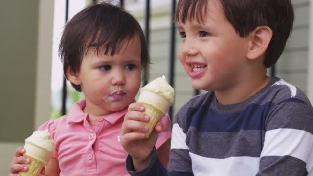 fratello e sorella mangiare coni gelato insieme - portico video stock e b–roll