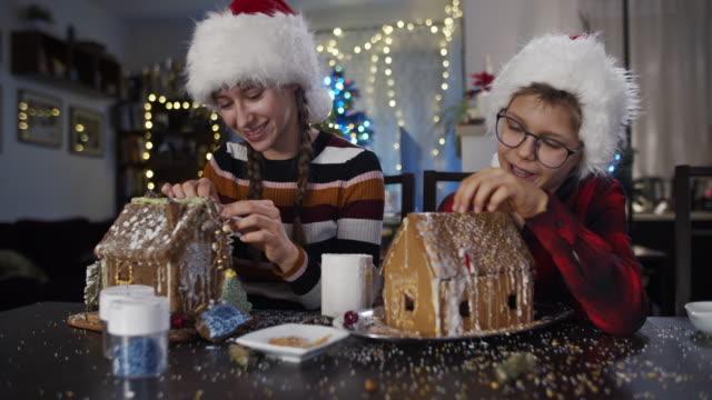 bruder und schwester mit spaß beim dekorieren von lebkuchenhäusern - lebkuchenhaus stock-videos und b-roll-filmmaterial