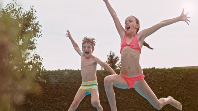 vídeos y material grabado en eventos de stock de cámara lenta de las hermanas y hermano salto en piscina al anochecer - backyard pool