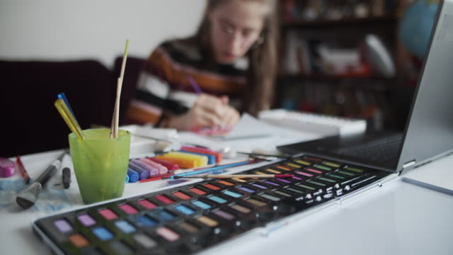 fratello e sorella imparano a dipingere a casa - arte video stock e b–roll