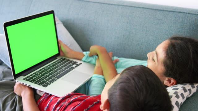 vídeos de stock e filmes b-roll de brother and sister lying on sofa at home using laptop computer - tv e familia e ecrã