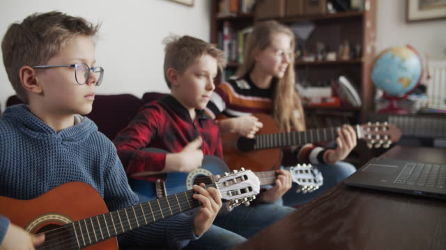 Brother and sister playing guitars together