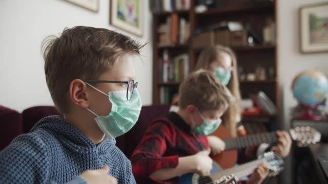 형제 와 자매 연주 기타 를 함께 - 초점 이동 스톡 비디오 및 b-롤 화면