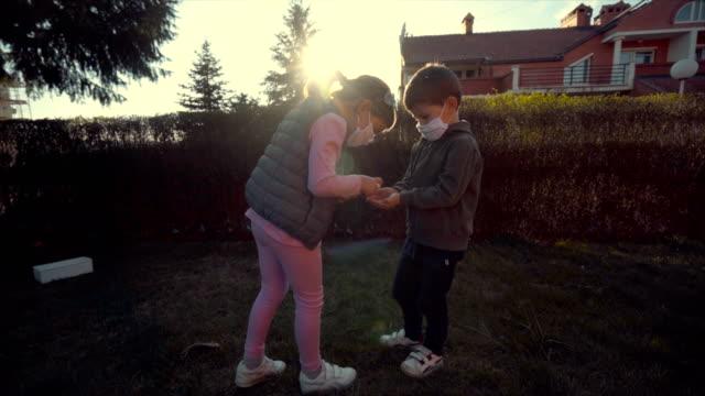 vidéos et rushes de frère et soeur jouant dans la cour arrière pendant la quarantaine de maison de coronavirus - enfant masque