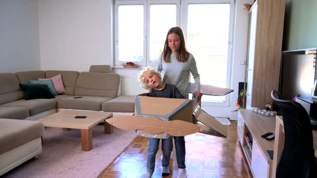Brother and Sister Playing with Cardboard Airplane Indoors
