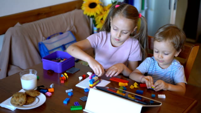 brother and sister playing with colorful bricks at home - brother stock videos and b-roll footage