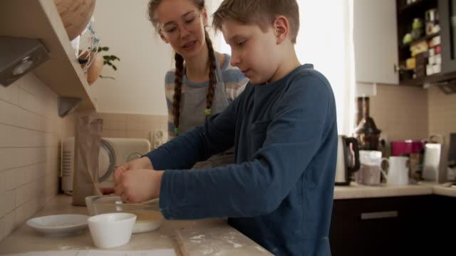 vídeos de stock e filmes b-roll de brother and sister preparing dough for bread buns - baking bread at home