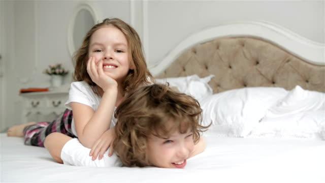 vídeos y material grabado en eventos de stock de hermano y hermana relajante juntos en la cama. los niños lindos son tener diversión en el dormitorio por la mañana - hermana