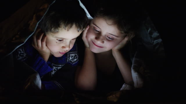 Brother and Sister Watching a Movie A brother and sister are lying on the floor under a blanket and are happily watching a movie on a digital tablet before bed. family watching tv stock videos & royalty-free footage