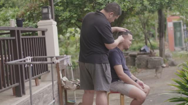 bruder macht haarschnitt zu seinem bruder zu hause. - friseur lockdown stock-videos und b-roll-filmmaterial