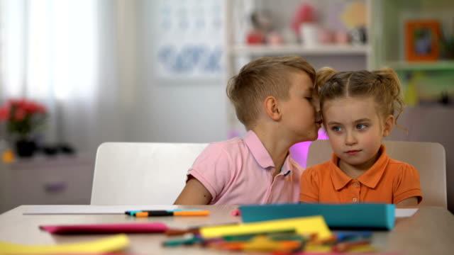 fratello sussurrando orecchio gemello segreto, comunicazione bambini, cattive notizie, pettegolezzi - ear talking video stock e b–roll