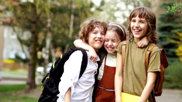 Brothers and sister cheerfully embrace each other on the way to school. Day of knowledge. Back to school. Family education video