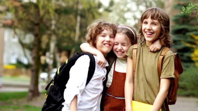 Frères et soeur joyeusement embrassent sur le chemin de l'école. Jour de la connaissance. Retour à l'école. Éducation familiale - Vidéo
