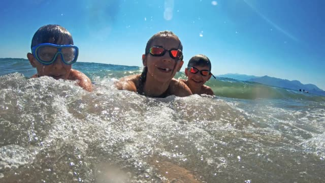 Brothers and sister having fun splashed in sea Little boys and teenage girl are having fun lying on beach and being splashed by waves. Candid smile and laughter. candid stock videos & royalty-free footage