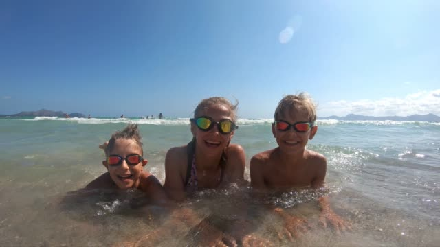 Brothers and sister having fun splashed in sea