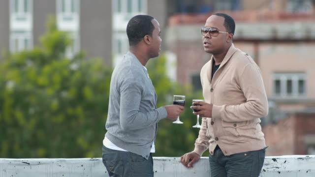 vidéos et rushes de hd: frères boire du vin sur la terrasse sur le toit - man drinking terrace