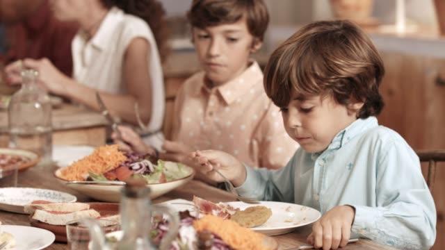 vídeos y material grabado en eventos de stock de hermanos tener comida en la mesa durante el partido - comida española
