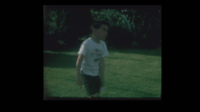 1965 Brothers playing badminton in backyard video