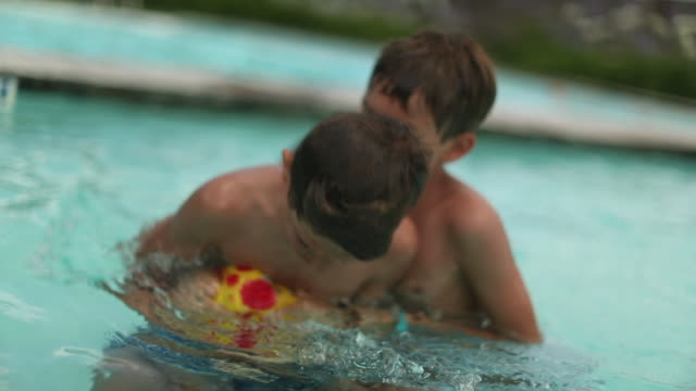 brothers playing hand-ball at swimming pool during summer day outdoors. children fighting and competing for ball inside water - рука человека стоковые видео и кадры b-roll