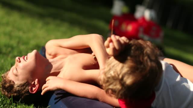 兄弟は裏庭で外で喧嘩をする。屋外でお互いに戦う兄弟 - 兄弟姉妹点の映像素材/bロール