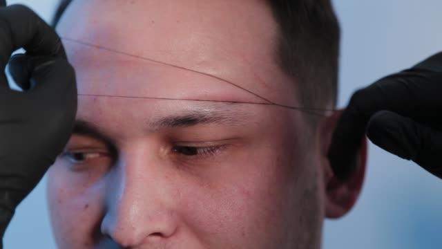 vidéos et rushes de browist fait la correction de sourcil avec un fil à un homme dans un salon de beauté - sourcils