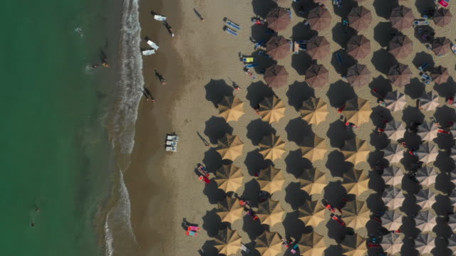 Brown Beach Umbrellas To White Beach Umbrellas On The Right And The Water On The Left Downward Drone Footage