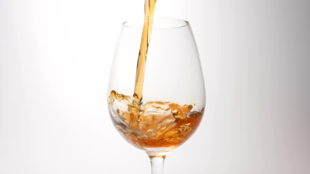 SLOW MOTION: Brown beverage pour into a glass on a white background video