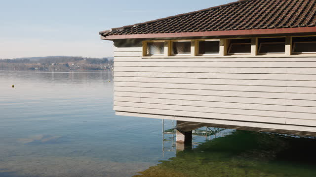 brown boathouse exterior view, parking possibility, in the background a lake, the house reflected in the blue water, bright sunshine, daytime, without people, close up view