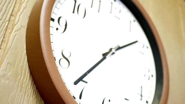 Brown clock ticking on wall in a ambient hallway Brown clock ticking on wall in a ambient hallway wall clock stock videos & royalty-free footage
