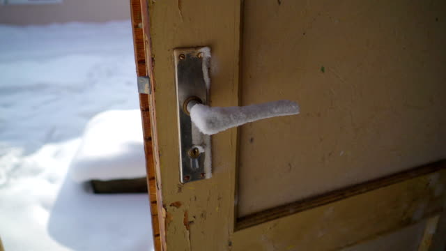 A brown door with the door knob covered with ice video