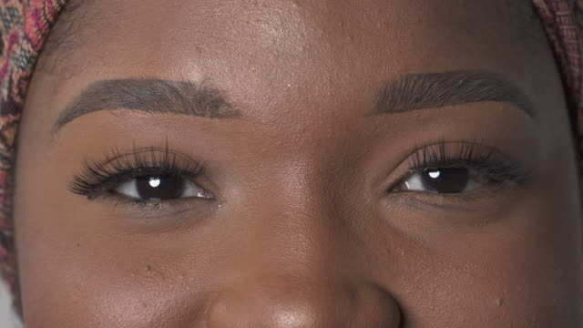 vídeos de stock e filmes b-roll de brown female eyes looking at camera. close-up portrait shot of a beautiful african american woman - rímel