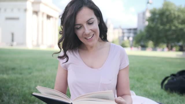 Bruinharige Kaukasische vrouw het lezen van een boek in het Park in Londen in de voorkant van Wellington Arch video