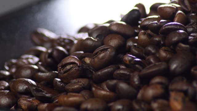 braune geröstete körner kaffeebohnen gyrating in einem schwarzen tablett - koffeinmolekül stock-videos und b-roll-filmmaterial