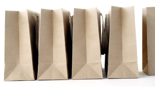 brown shopping bags on white background - borsa della spesa video stock e b–roll