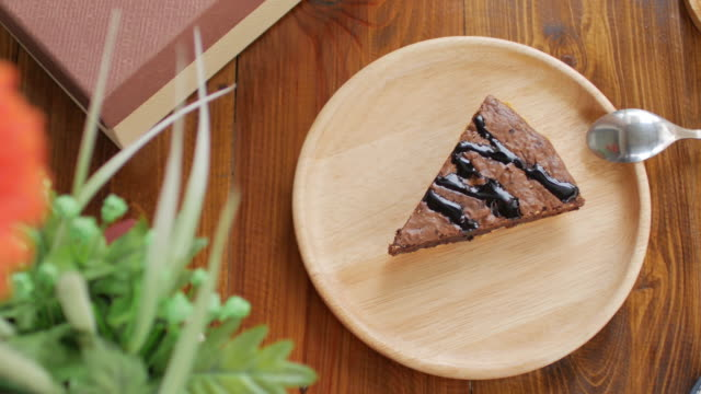 Brownie chocolate cake on wooden plate with coffee in cafe , dolly shot video