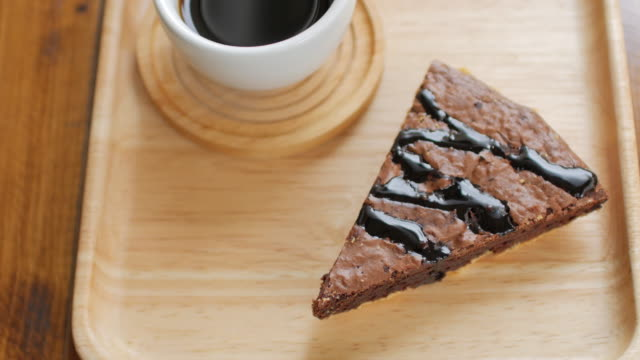 Brownie chocolate cake on wooden plate with coffee in cafe , dolly shot left to right video