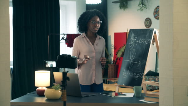 brown-skinned nauczyciel daje lekcję online z domu podczas covid-19 blokady. - instruktor filmów i materiałów b-roll