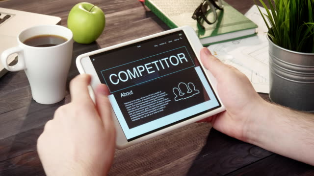 Browsing competitor's web page using digital tablet at desk