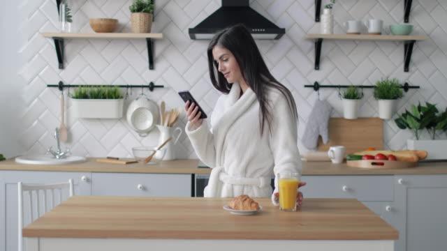 vidéos et rushes de naviguer sur internet dans la cuisine - peignoir