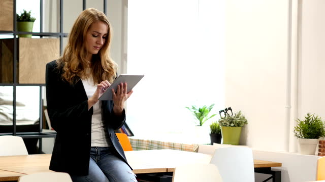 Browsing Online on Tablet by Businesswoman Sitting on Desk video