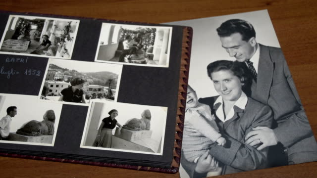 Browsing  vintage album with mom, dad and son FDV