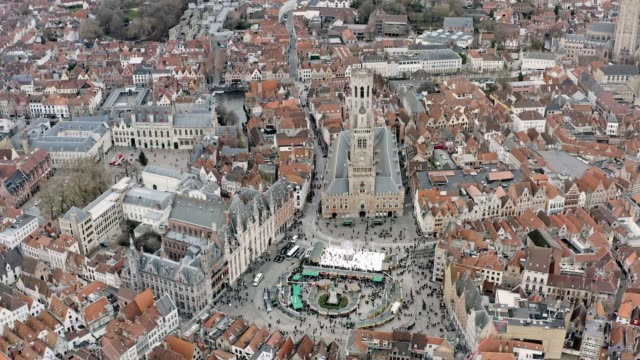 bruges aerial city view feat. belfry of bruges and market square - bruges video stock e b–roll