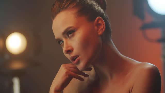 vídeos y material grabado en eventos de stock de actriz morena con hermoso maquillaje de ojos con luz brillante gira lentamente la cabeza y toca su cuello con la mano, mirando hacia adelante. - feminidad