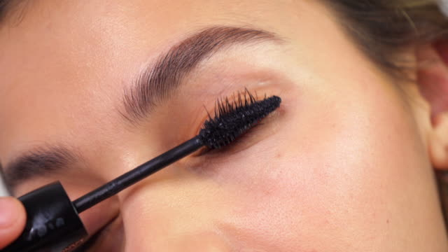 Brunette applying makeup on eyelashes. Confident and attractive woman applying mascara. Closeup beauty makeup. Brunette applying makeup on eyelashes. Confident and attractive woman applying mascara. Closeup beauty makeup. mascara stock videos & royalty-free footage
