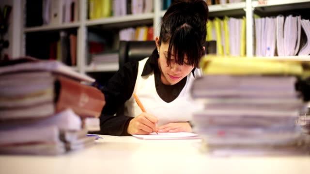 Brunette businesswoman among piles of files video