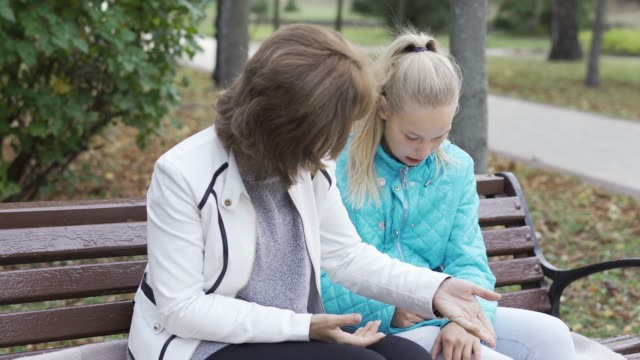 Brunette caucasian grandmother and her young blond granddaughter sitting at the bench and talking