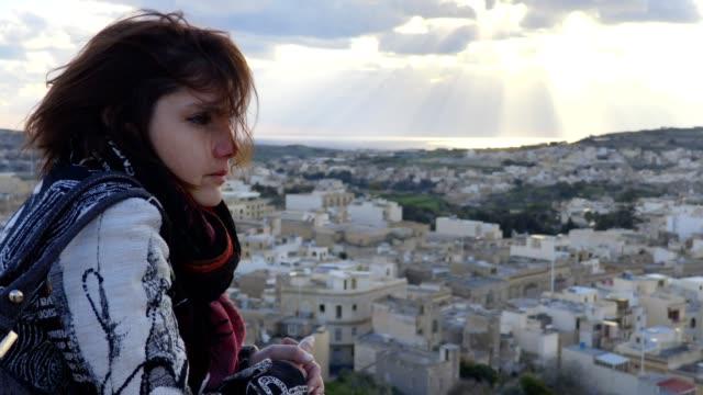 Brunette contemplates the city view on a windy day- Valletta, Malta video