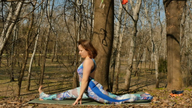 Brunette doing a split on carpet in the park video