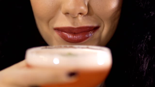 brunette drinks cocktail and smiles to camera - happy hour stock videos and b-roll footage