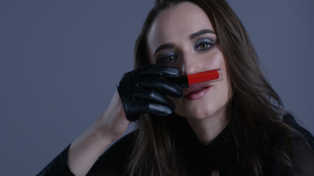 Brunette fashion model holds red lipstick in her hand, smelling it. Fashion video. Brunette fashion model holds red lipstick in her hand, smelling it. Fashion video. Slow Motion. 4K 30fps ProRes 4444 lip liner stock videos & royalty-free footage